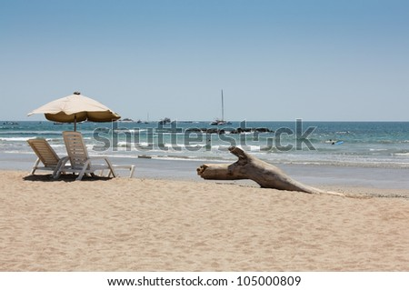 Two empty beach chairs next to a piece of driftwood and shaded by an umbrella face the Pacific beach of Costa Rica with surfers and boats in the blue water.