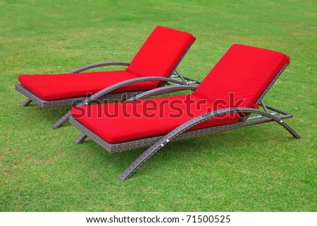 Two empty beach chairs on the grass