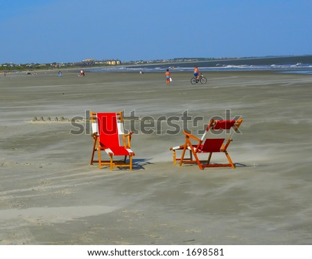 two empty chairs on a busy beach