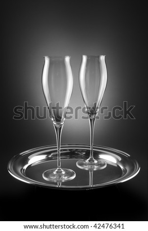 Two empty crystal champagne flutes shot on silver serving tray