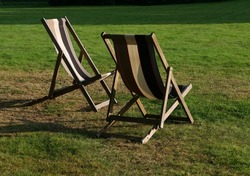 Two empty deckchairs on grass in evening sunshine with shadows
