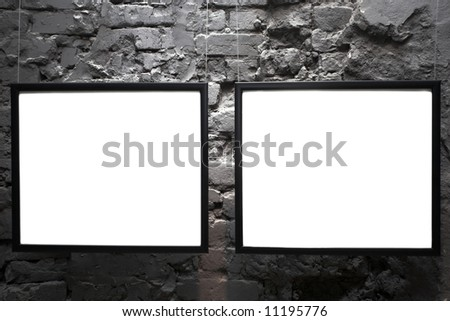 Two empty frames on brick wall in museum