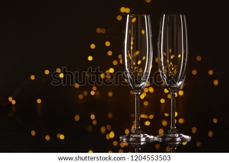 Two empty glasses for champagne on a dark background with LED lights garland. Copy space for text. #1204553503