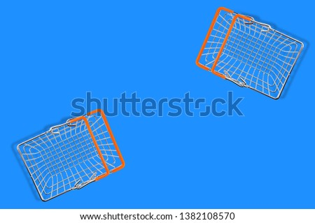 Two empty market baskets made from chrome metal wire and orange rubber handles lying on blue table. Top view. Copy space for your text. Concept of business or consumerism