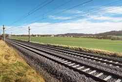 Two empty railway tracks under a blue sky, through nature. German railroad lines with a diminishing perspective. No traffic.