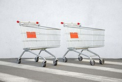 Two Empty Shopping Cart Trolley Stands near Mall with Copy Space. Grocery Cart on a White Wall Store Background. Couple Trolleys near Supermarket. E-commerce. Shopping Concept. Side View. Buy Online