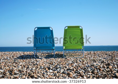 Two empty sunbeds on pebble beach (landscape)