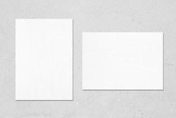 Two empty white vertical and horizontal rectangle poster mockups with soft shadows on neutral light grey concrete background. Flat lay, top view