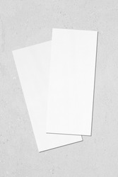Two empty white vertical rectangle price-list or menu mockups with soft shadows lying diagonally on top of each other on neutral light grey concrete wall background. Flat lay, top view