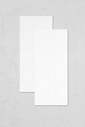 Two empty white vertical rectangle price-list or menu mockups with soft shadows lying on top of each other on neutral light grey concrete wall background. Flat lay, top view