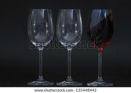 two empty wine glasses with an oblique full red liquid