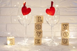 two empty wine glasses with red hearts attached against the white brick wall, a garland is shining inside the glasses, next to glasses of cubuts with letters laid out the phrase I love you
