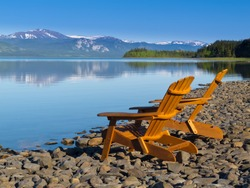 Two empty wooden Adirondack chairs or Muskoka deckchairs on stony shore overlooking scenic calm Lake Laberge, Yukon Territory, Canada, with snowcapped mountains in the distance