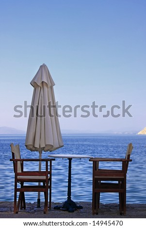 Two empty wooden chairs on the edge of the ocean (Greek islands).