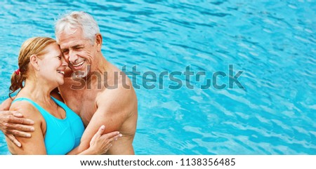 Two enamored seniors as a couple in hotel pool on vacation in summer #1138356485
