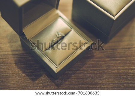 Two engagement ring in box on wood table