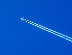 Two engined airplane flying through blue sky with vapor trails