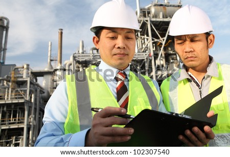 two engineer oil industry discussing a new project with large oil refinery background