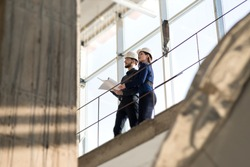 Two engineers, a man and a woman in construction helmets looking at a construction project. In white construction helmets standing on a construction bridge. Photographed from below.