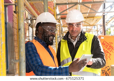 Two engineers, an African American and a caucasian, wearing orange and yellow safety jackets and helmets, working with tablet computer among scaffolding on construction site