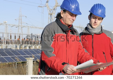 Two engineers in a solar panel site - stock photo
