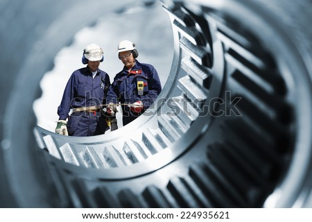 two engineers seen through a large cogwheels gear shaft, metal industry #224935621