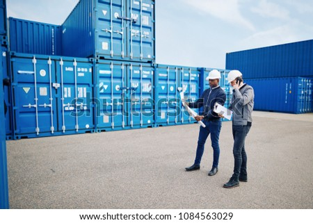 Two engineers standing by freight containers in a commercial shipping yard reading blueprints and talking on a cellphone