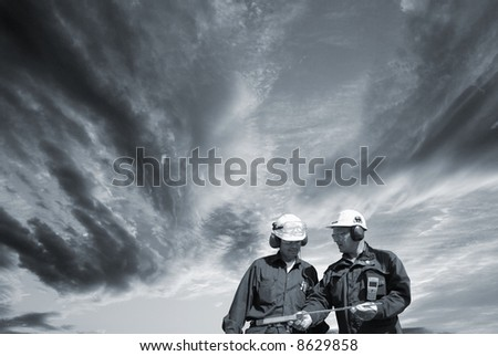 two engineers walking under a dark stormy sky, conceptual idea in a dark toning concept