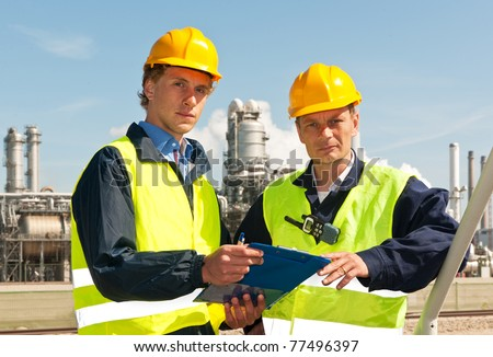 Two engineers, wearing reflective clothing and a hard hat, looking up from the note board they have been discussing