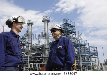 two engineers with hard hats and protective clothing in front of large oil-refinery