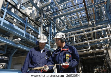 two engineers with hard-hats standing in front of refinery and miles of pipelines