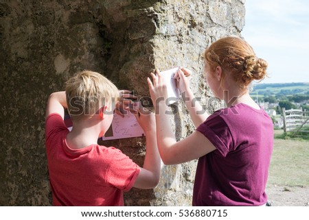 Two English children use pencils to take etchings from the surface of a stone wall in the countryside #536880715