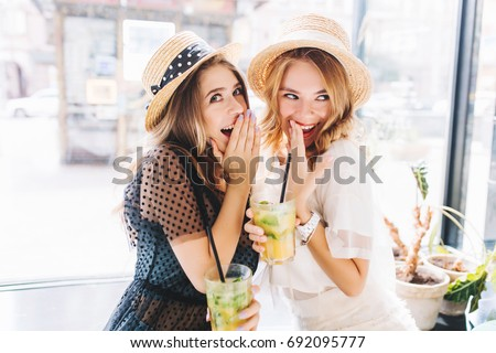 Two enthusiastic ladies sharing secrets and covering faces with hands while drink cocktails in cafe. Outdoor portrait of gossip girls in trendy hats having fun together and posing beside big window.