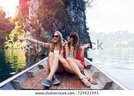 Two enthusiastic women, best friends exploring wild nature of Khao Sok national park.  Sitting in wood long tail boat on tropical limestone cliffs background. Lifestyle image. Island lagoon.
