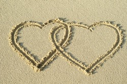 Two entwined hearts drawn in the sand of a beach representing love, valentine, romance.