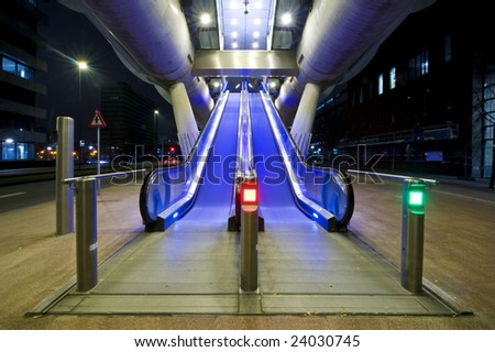 Two escalators, leading up towards the entrance of the platform of an elevated tram line