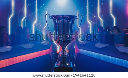 Two Esport Teams of Pro Gamers Play to Compete in Video Game on a Championship. Stylish Neon Cyber Games Online Streaming Tournament Arena with Trophy in the Center. Photo stock ©