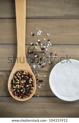 Two essential spices, peppercorns and sea salt on a wooden background