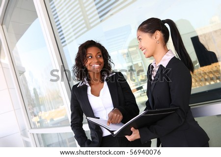 Two ethnic asian and african business women team at office building