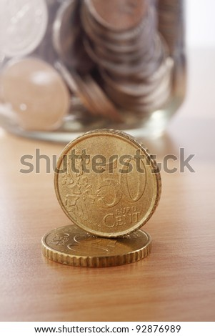 two Euro coin in front of the saving jar