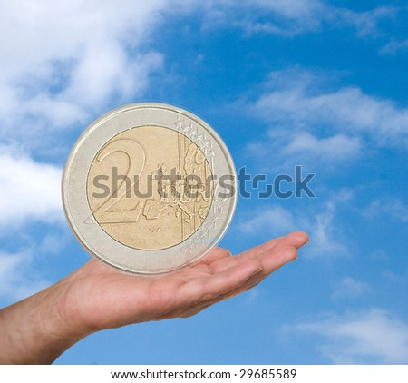 Two euro coin in hand on sky background background