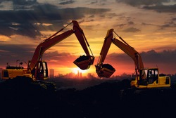 Two Excavators are digging the soil in the construction site on the sky sunset with cityscapes background