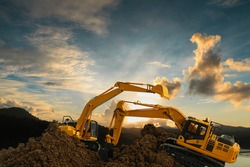 Two Excavators are digging the soil in the construction site on the  sunset  background