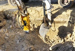 Two excavators in action to perform an excavation in rock. One with hydraulic hammer destroys the rock and the other with the machine loads a truck