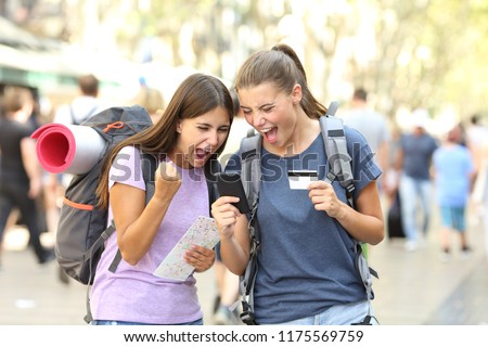 Two excited backpackers buying online with credit card and a smart phone in the street