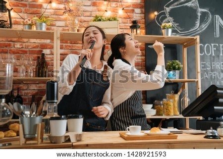 Two excited female colleagues in aprons working in cafe bar counter singing and dancing. relaxed woman waitresses holding bread tongs and pen as microphone. group lady barista coworkers enjoy music.