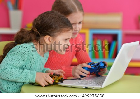 Two excited girls playing game on laptop