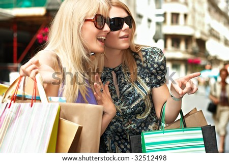 Two excited shopping woman point away in the city.
