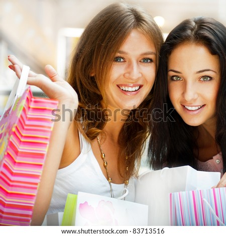 Two excited shopping woman resting on bench at shopping mall looking at camera