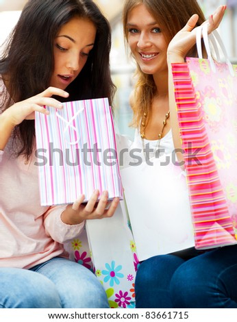 Two excited shopping woman resting on bench at shopping mall. Looking into shopping bags